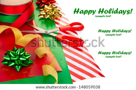 Wrapping Christmas presents, wrapping paper, ribbon, bows & scissors on white - stock photo