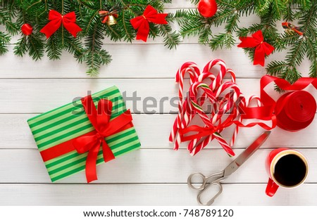 Wrapping gifts background. Handmade christmas present box and bunch of candy cane lollipops bound with red ribbon. Top view of white wooden table with fir tree branches border, copy space