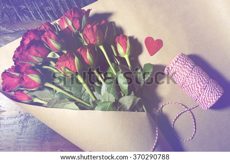 Wrapping Valentine red roses in brown paper on dark wood background, with applied retro vintage style filters. - stock photo