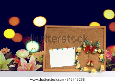 Wreath and card on cork board with artificial florist with blur bokeh background - stock photo