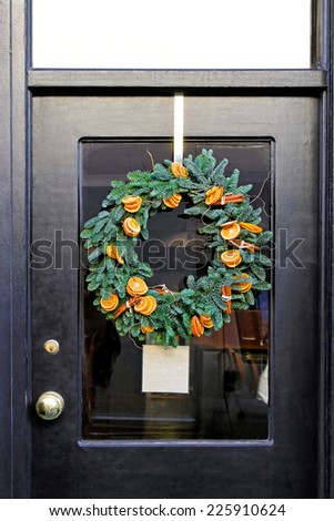 Wreath decoration with dry oranges and evergreen branches hanging on glass door  - stock photo