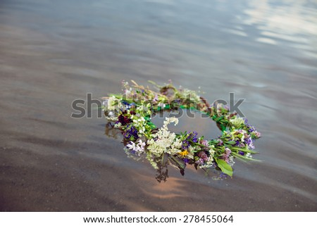Wreath floating on water, tradition Kupala night pagan rituals - stock photo