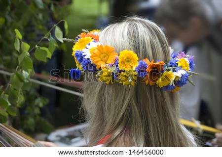 Wreath from wild flowers on the head at the girl. - stock photo