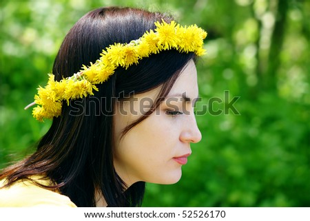 Wreath on a head of the girl sitting in a wood
