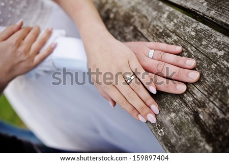 Wreathed hands of lovers. Hands of spouses being in the amorous touch on the wooden railing of stairs - stock photo