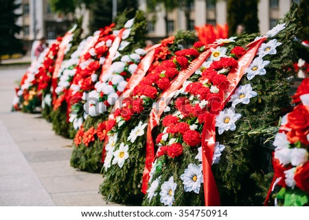 Wreaths and flowers lie on a communal grave of Soviet soldiers who died during the liberation of Gomel and Belarus from German invaders in World War II. - stock photo