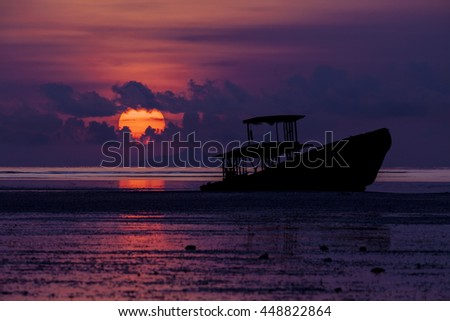 wreck boat on beach at sunrise or sunset.