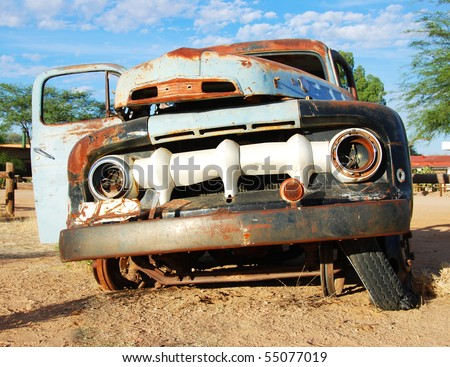 Wreck of an old car in a field - stock photo