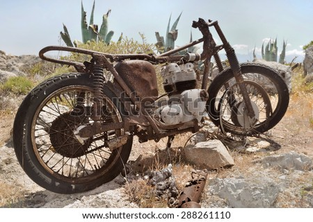 wreck of an old rusty bike in the rocks - stock photo
