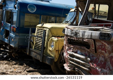 Wrecked buses and truck in a junkyard - stock photo