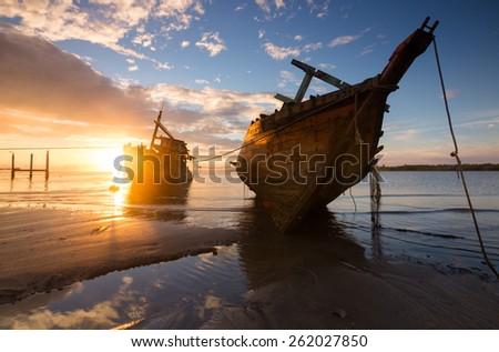 Wrecked fishing boat with sunrise at Kuala Penyu, Sabah, Borneo, Malaysia - stock photo