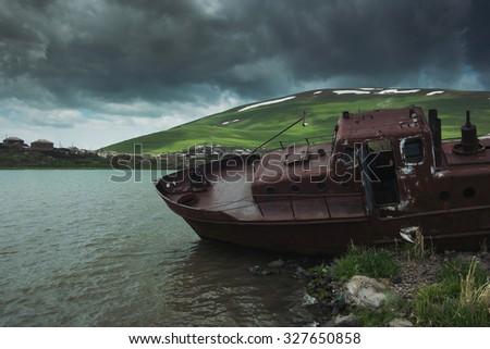 Wrecked rusty abandoned fishers boat. Tabaskuri lake, Georgia - stock photo