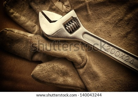 Wrench and gloves. - stock photo