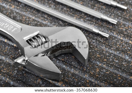 Wrench and screwdriver on spotted metal background