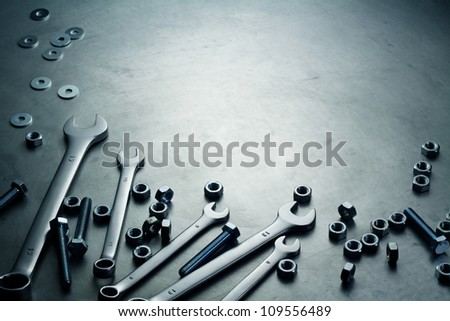 Wrench, nut and screw on a metal plate