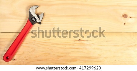 Wrench on wooden background - stock photo