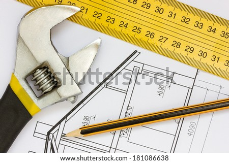 Wrench, ruler and pencil on the building blueprints
