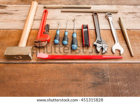 Wrench, screwdriver, Phillips screwdriver, flat crowbar,brass hammer,pipe wrench,punch,Hex wrench on wood background with copy space. - stock photo