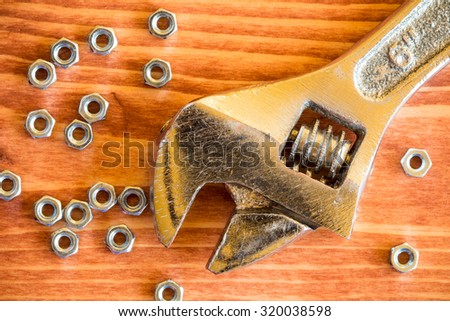 Wrench tool and nuts on the wooden background - stock photo