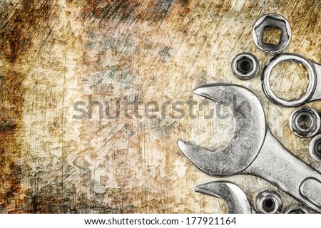 Wrench tools and nuts on a vintage metallic background with space for text - stock photo