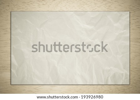 Wrinkle recycle paper on wood board. - stock photo