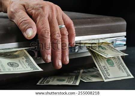 wrinkle senior hand touch suitcase full of dollar cash in dark room, Concept of saving for retirement - stock photo