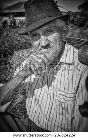 Wrinkled and expressive old farmer leaning on an apple tree in the yard. Black and white picture. Close-up. - stock photo