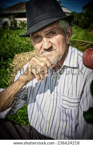 Wrinkled and expressive old farmer leaning on an apple tree in the yard. Close-up. - stock photo