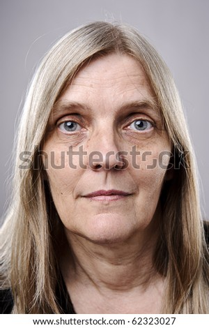 wrinkled blonde woman poses for a portrait in studio - stock photo