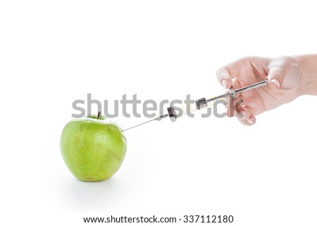 Wrinkled green apple and syringe in female hand on white background. Beauty cosmetology skincare and genetic modification concept - stock photo