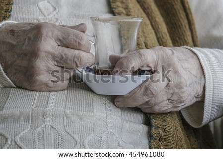wrinkled hand of a senior person holding a glass