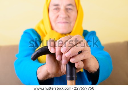 wrinkled hands of old woman on stick - stock photo