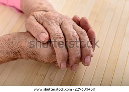 wrinkled hands of old woman on table - stock photo