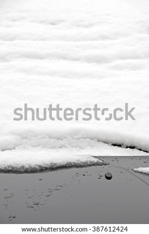 Wrinkled softened snow crawling down the covered windshield of a car - stock photo