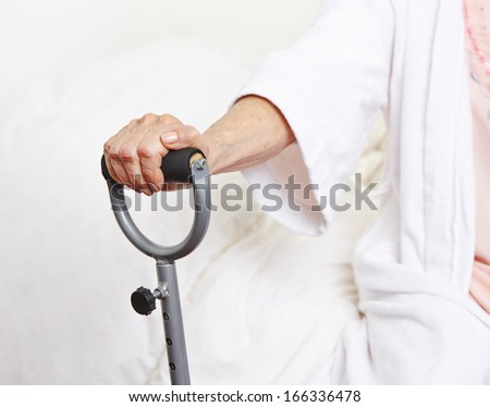 Wrinkly hand of senior woman holding cane in nursing home - stock photo