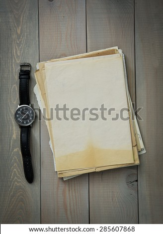 Wrist Watch and Old paper on a wooden background