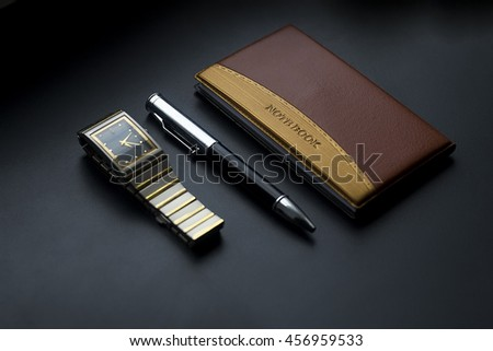 wrist watch,Notepad and pen on black background