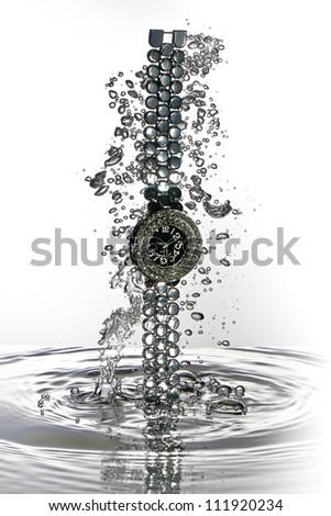 Wrist watch water splash necklace, high speed water splash - stock photo