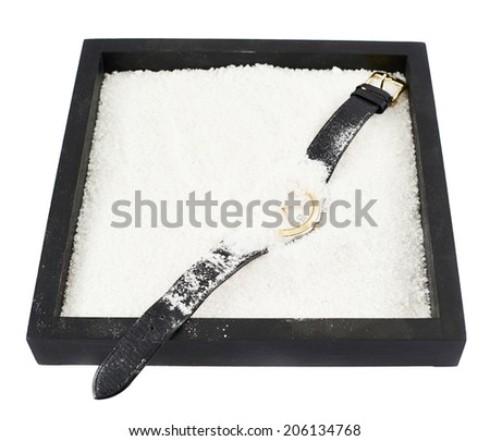 Wristwatch in a sandbox composition isolated over white background