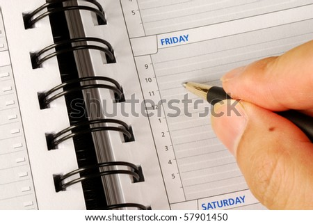 Write down what to do on Friday in the day planner - stock photo