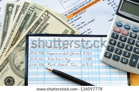 Write some checks to make payments for household expenses - stock photo