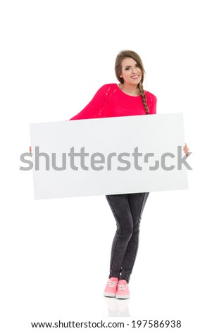 Write your message at the banner. Smiling girl is holding blank placard. Full length studio shot isolated on white.