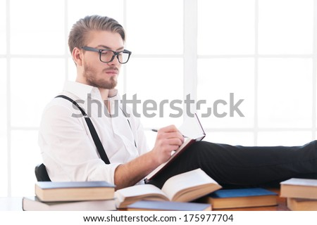 Writer at work. Handsome young man in shirt and suspenders writing something in notebook while sitting at his working place - stock photo