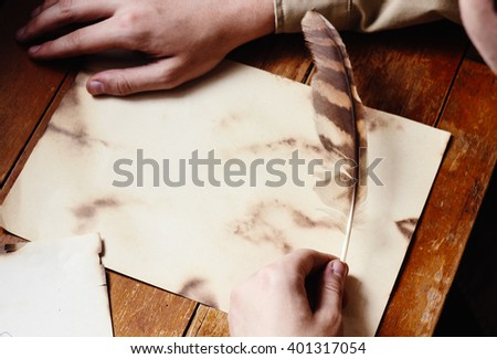 Writer holding quill near blank clean parchment paper space for text