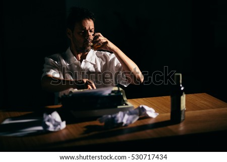 Writer novelist drinking whiskey working on a book using typewriter