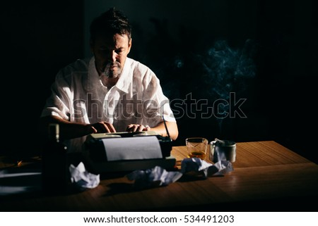 Writer novelist smoking working on a book late using typewriter
