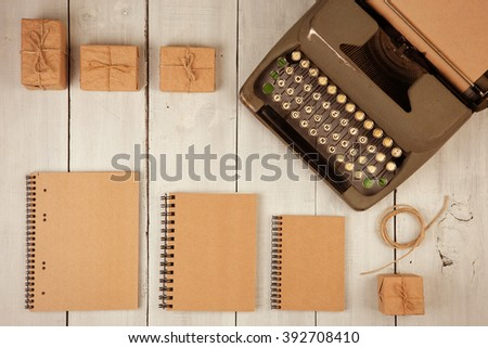Writer's workplace - vintage typewriter, notepads, present boxes on the white wooden background  - stock photo