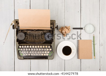 writer's workplace - wooden desk with vintage typewriter  and other supplies