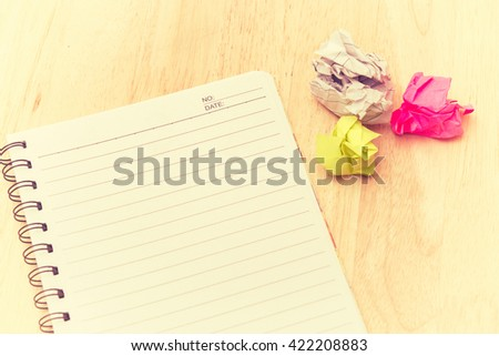 Writers Block. Paper lump. on wooden background.vintage tone.