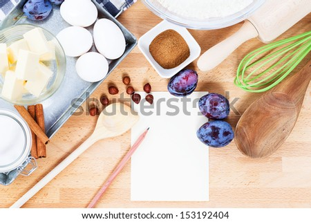 writing a recipe for plum cake with baking ingredients and tools from top with paper and a pencil - stock photo
